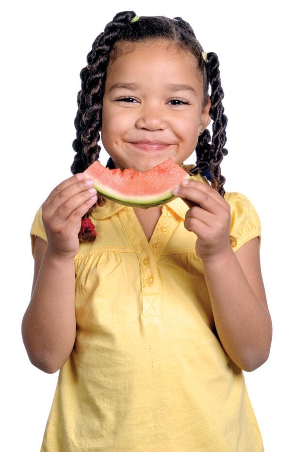 Une jeune fille souriante qui mange un morceau de melon d'eau