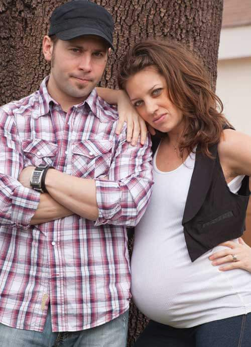 A pregnant women leaning on her partner. His arms are crossed. They are in front of a tree.