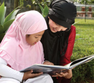 A young girl is sitting outside reading a book to her mother