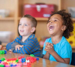 Deux jeunes enfants assis à une table avec de beaux sourires
