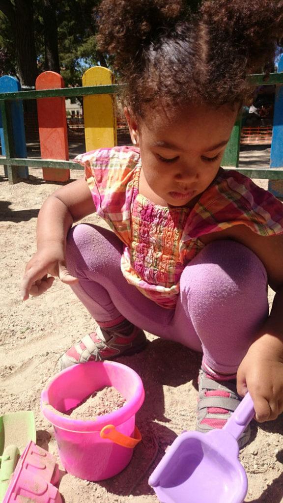 Jeune fille qui joue dans le sable
