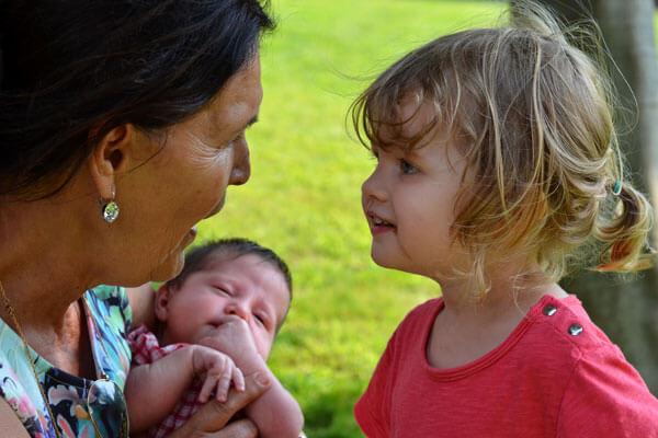 Un enfant en bas âge qui regarde de près une femme âgée qui tient un bébé